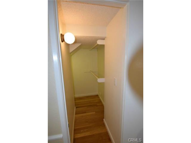 Large storage closet under the stairs has hardwood floors and wr